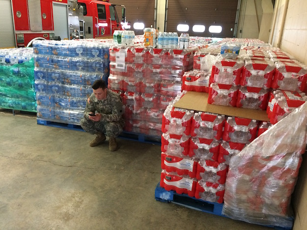 U.S. Army service member crouching next to pallets of water bottles in Flint, Mich.