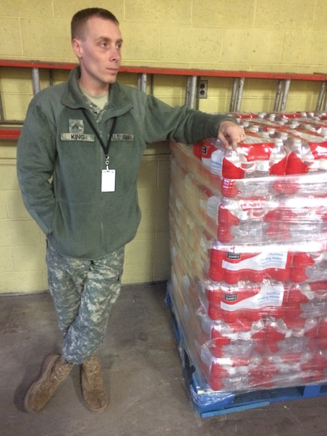 Corporal Jack King leans against a pallet of water bottles in Flint, Mich.