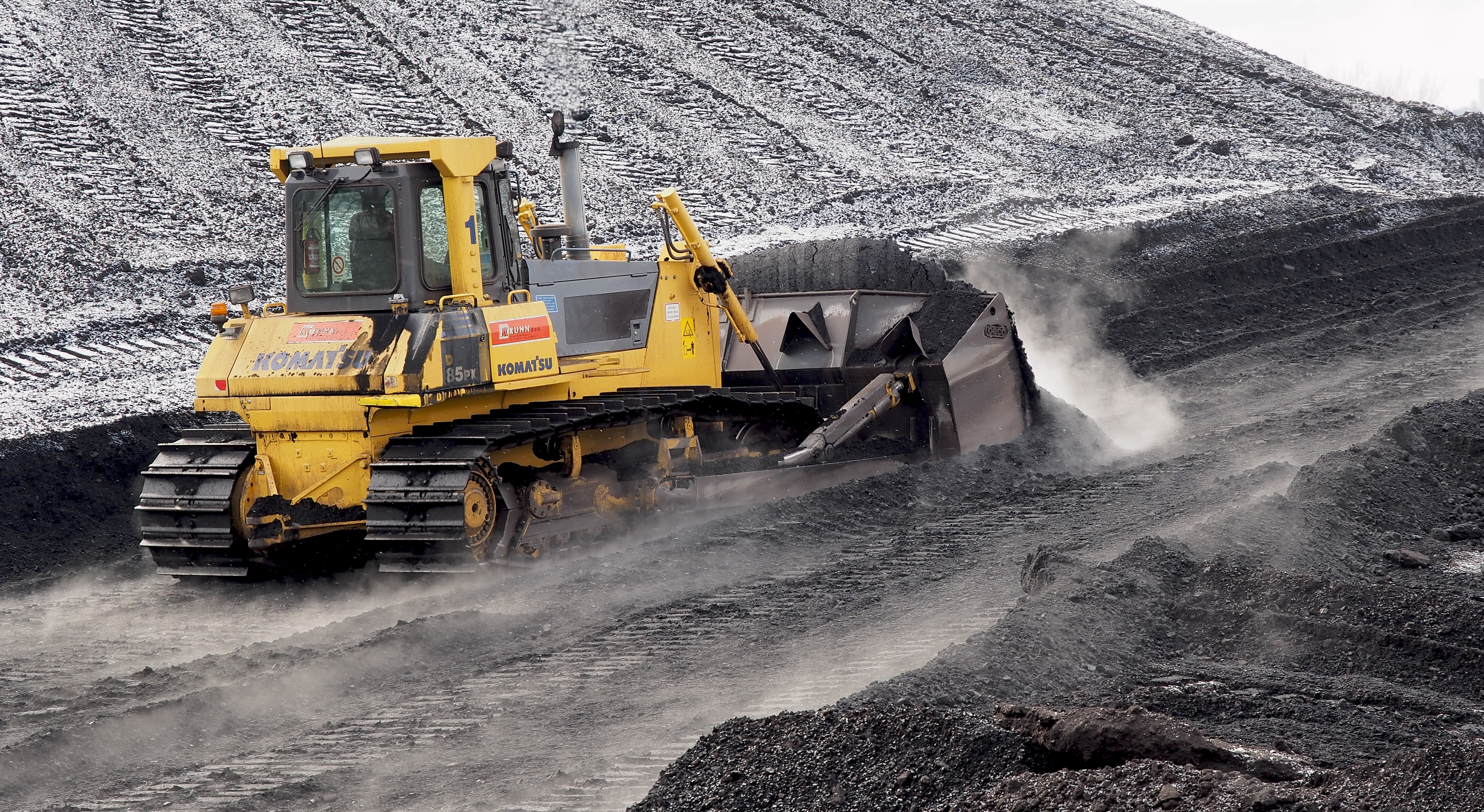 A bulldozer pushing coal.