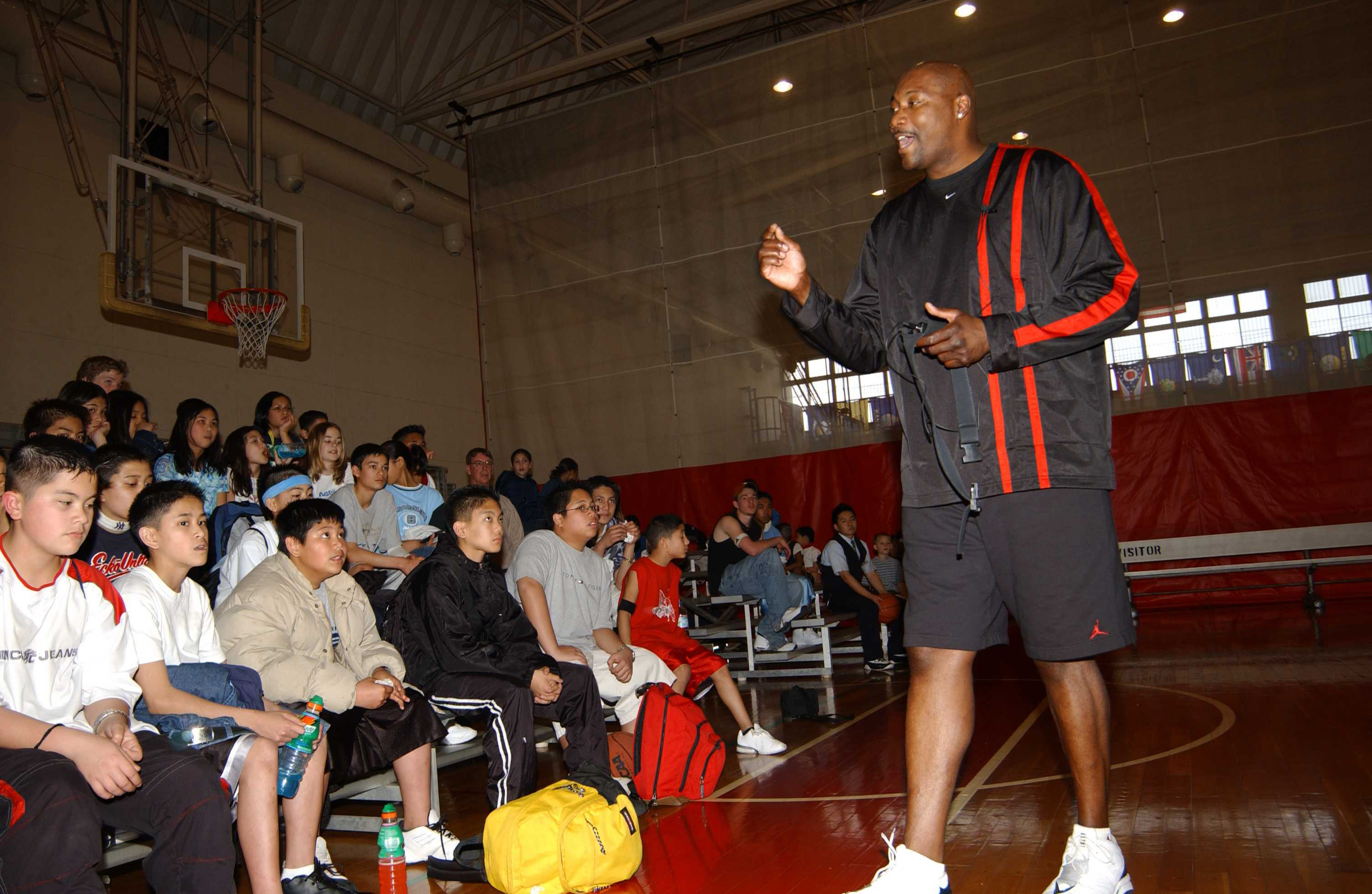 Former NBA player Jerome Kersey addresses a group of kids on the basketball court in the Naval Air Facility, Ranger Gym