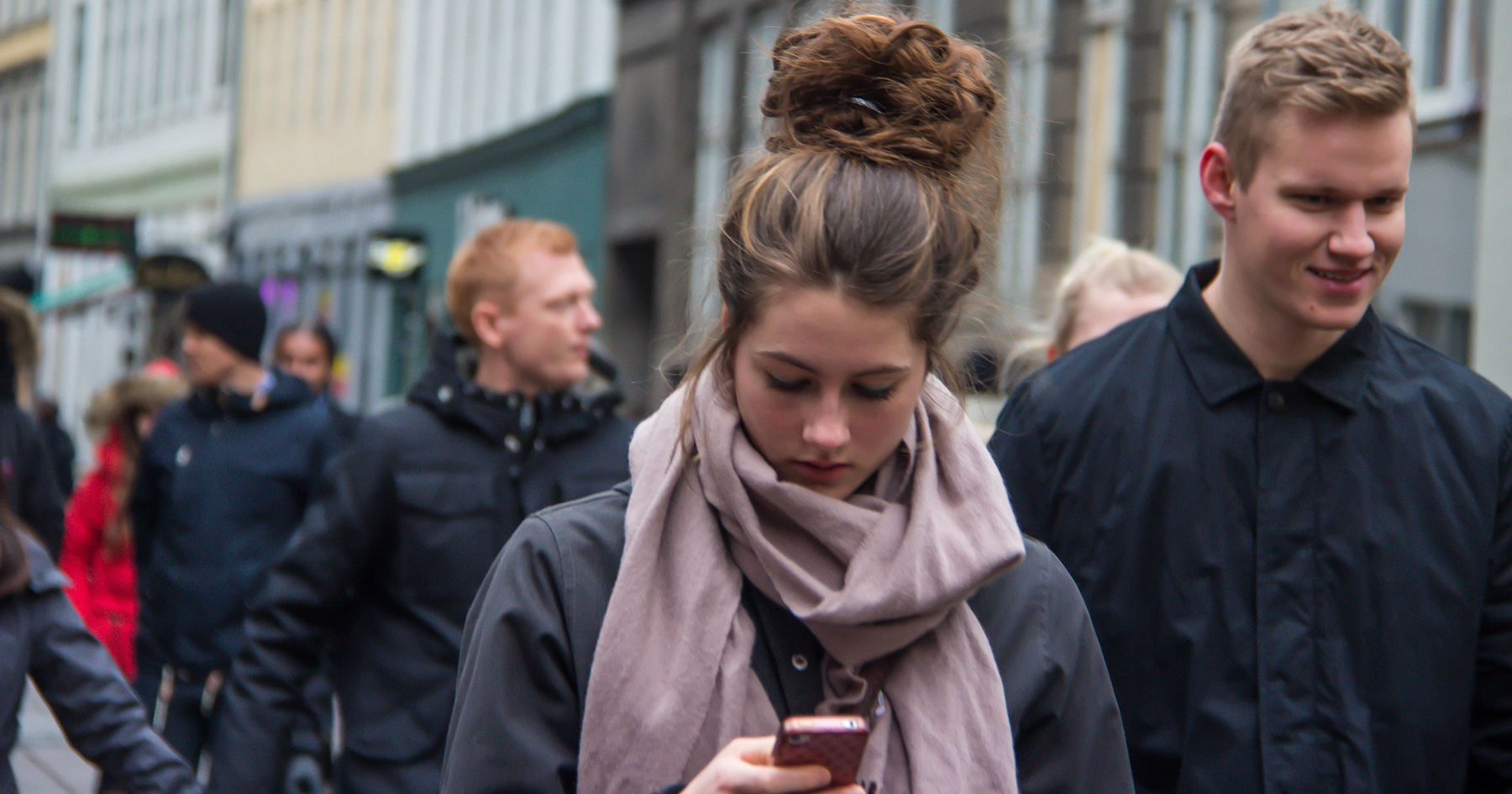 Young woman in a crowd checking her phone