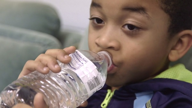 Young Flint resident drinking bottled water.