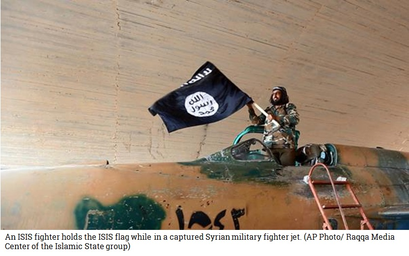 An ISIS fighter holds the ISIS flag while standing in a captured Syrian military fighter jet. (AP Photo/ Raqqa Media Center of the Islamic State group)