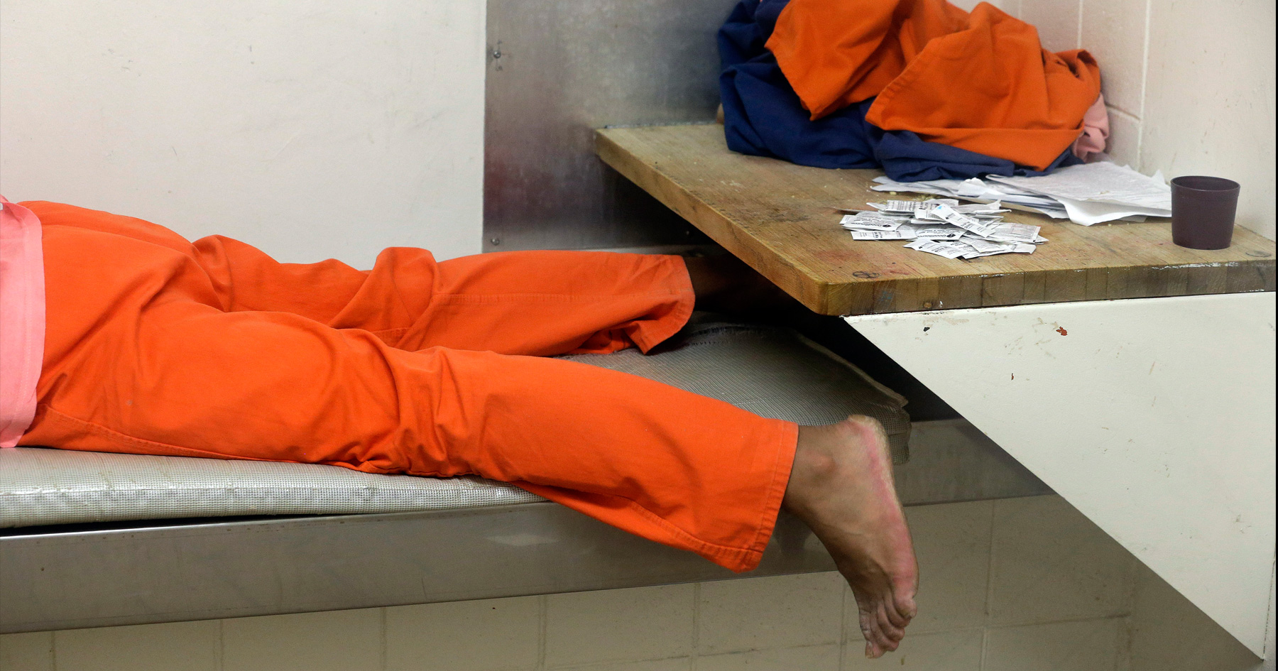 Inmate lying down on their bed in prison cell