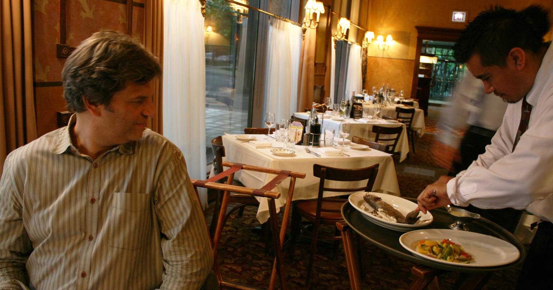 Man watching a restaurant worker serve food