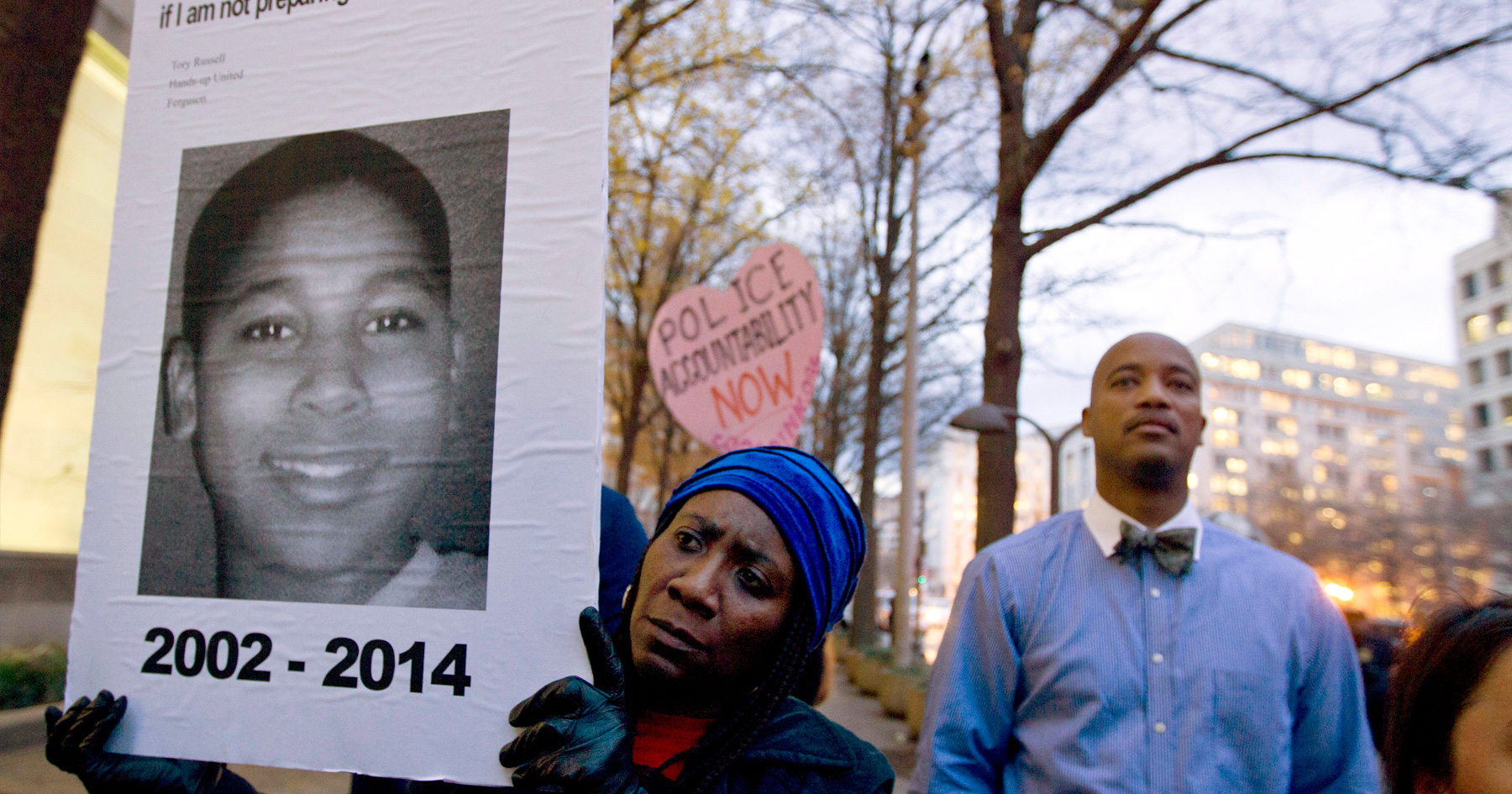 FILE - In a Monday, Dec. 1, 2014 file photo, Tomiko Shine holds up a picture of Tamir Rice, the 12 year old boy fatally shot on Nov. 22 by a rookie police officer, in Cleveland, Ohio, during a protest.